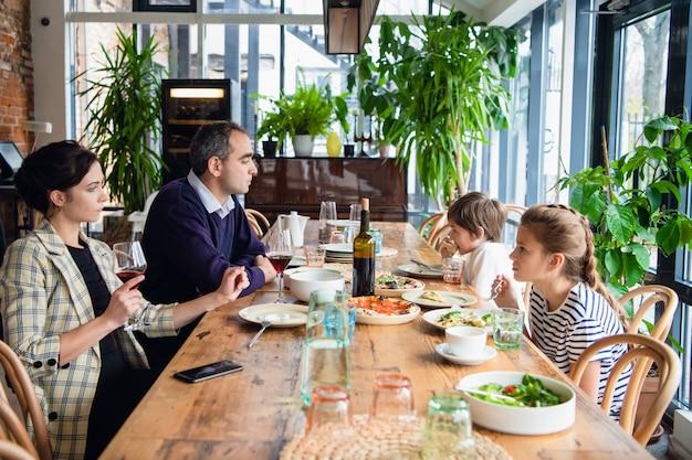 Семья с детьми в кафе, родители пьют вино.