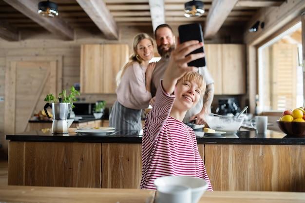 Семья с маленькой дочерью, делающей селфи во время приготовления еды в частной квартире на зимних каникулах