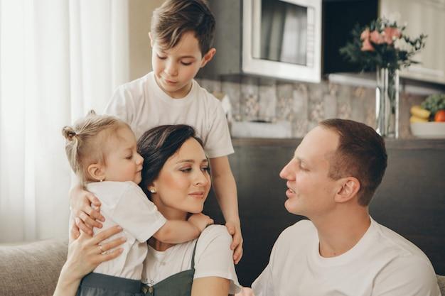 2人の子供を持つ家族がソファーに座っています。自宅で週末。一緒に時間を過ごす