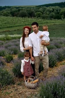두 명의 멋진 자녀를 둔 가족이 라벤더 밭을 걷고 있습니다.