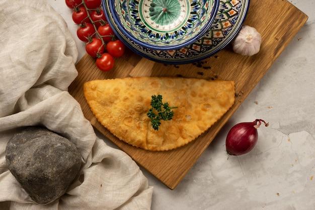 Известное русское блюдо - горячий чебурек с мясом, овощами и зеленью рядом с декоративными национальными узбекскими керамическими блюдами с традиционным узором.