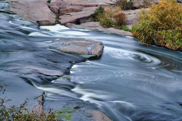 Среди белых мокрых камней, покрытых пожелтевшей золотистой травой, прохладной осенью на живописной природе украины бежит фантастический быстрый ручей.