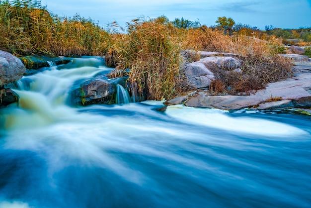 Среди белых мокрых камней, покрытых пожелтевшей золотистой травой, прохладной осенью на живописной природе украины бежит фантастический быстрый ручей