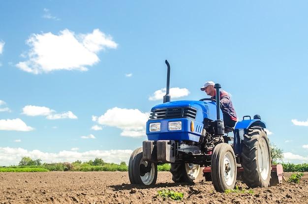 농부가 농장 필드에서 트랙터를 운전합니다.