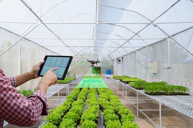 농부 정원사가 농산물 무인 항공기를 검사하기 위해 태블릿을 들고 프리미엄 사진