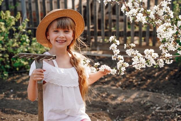 정원에 있는 모자를 쓴 한 농부 소녀가 정원에 살구꽃이 활짝 피었습니다.