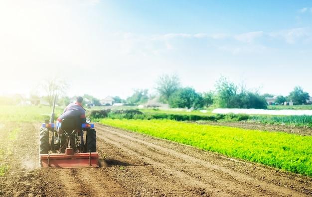 トラクターの農民は、新しい植栽の前に畑を耕します。