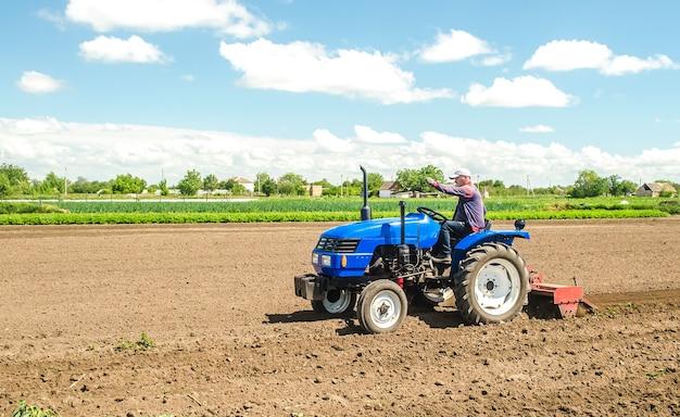 제 분소가있는 트랙터의 농부가 추가 파종을 위해 토양을 분쇄하고 처리합니다.
