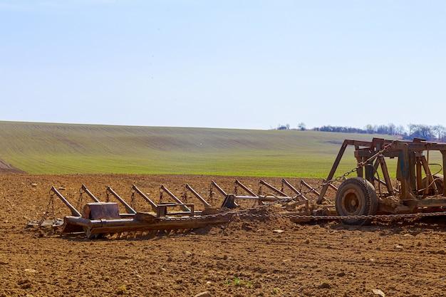 농부가 트랙터에 끌 쟁기로 들판의 흙을 쟁기질합니다. 필드에 쟁기와 농업 트랙터입니다.