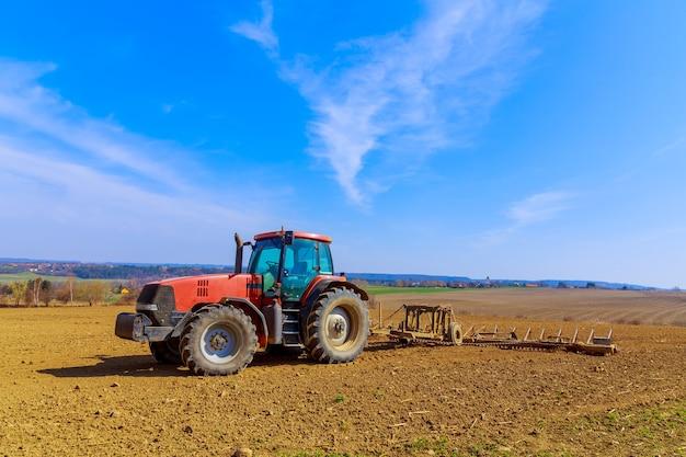 농부가 트랙터에 끌 쟁기로 들판의 흙을 쟁기질합니다. 필드에 쟁기와 빨간 농업 트랙터.
