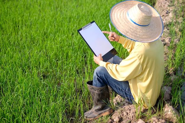 黄色の長袖シャツを着た農夫は、白紙のメモ帳を持って畑に座っています。