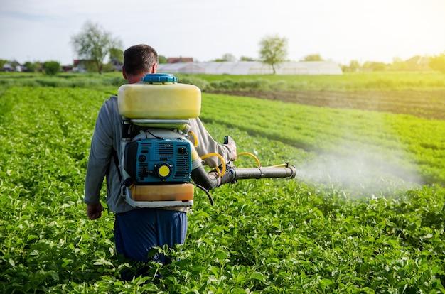 분무기를 가진 농부가 감자 덤불에 살균제와 살충제를 뿌린다
