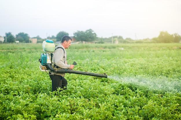 분무기 송풍기를 사용하는 농부가 해충 및 곰팡이 감염으로부터 감자 농장을 처리합니다.