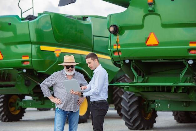 Фермер с трактором комбайн на поле при солнечном свете уверенных ярких красок