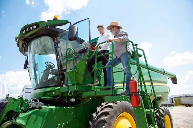 トラクターを持った農民が日光に自信を持って明るい色の畑で結合します