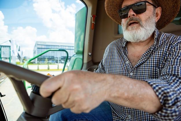 Фермер с трактором, комбайн на поле при солнечном свете. уверенные, яркие цвета