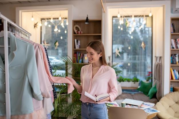 ピンクのコートの素材を調べるファッションデザイナー
