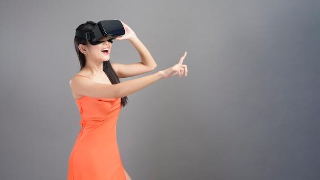 Модный портрет красивой женщины в оранжевом платье носит коробку виртуальной реальности, изолированную на сером.