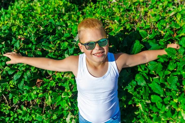 흰색 티셔츠와 검은색 안경을 쓴 세련된 소년이 녹색 덤불 배경에 서 있다