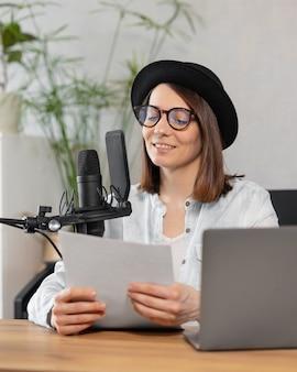 헤드폰과 마이크를 착용한 세련된 유럽 여성이 팟캐스트나 라디오 쇼를 녹음합니다.