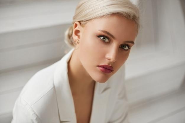 エレガントな白いスーツで完璧なブロンドの髪と完璧な流行のメイクでファッショナブルな若い女性