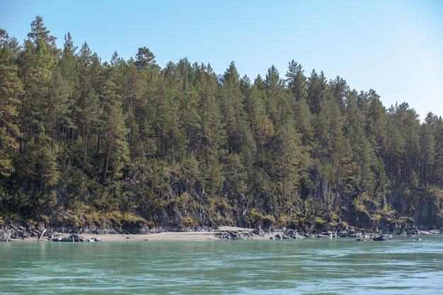 流れの速い広大な山川。大きな岩が水から突き出ています。アルタイ共和国のアルタイ山脈にあるターコイズ色の大きな山の川カトゥニ。