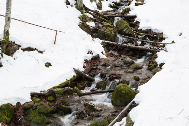 雪に覆われた2つの斜面の間を流れる速い渓流。
