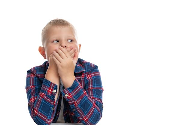 За столом сидит толстый грустный мальчик, прикрыв рот руками. школьник в клетчатой рубашке. обратно в школу. изолированные. крупный план.