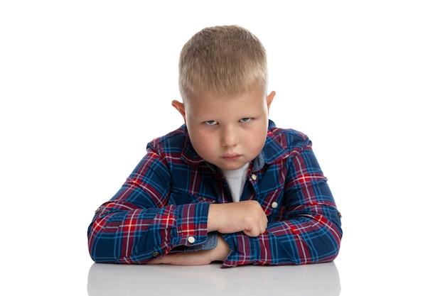 За столом сидит толстый грустный мальчик. школьник в клетчатой рубашке. обратно в школу. изолированные. крупный план.