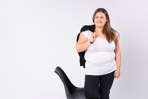 뚱뚱한 여자가 의자 근처에 서서 오른손에 재킷을 들고 좋은 분위기의 회색 배경을 가지고 웃고 있다