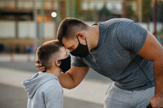 한 아버지와 아이가 일몰 동안 훈련을 받은 후 마스크를 쓰고 운동장에 서 있습니다.