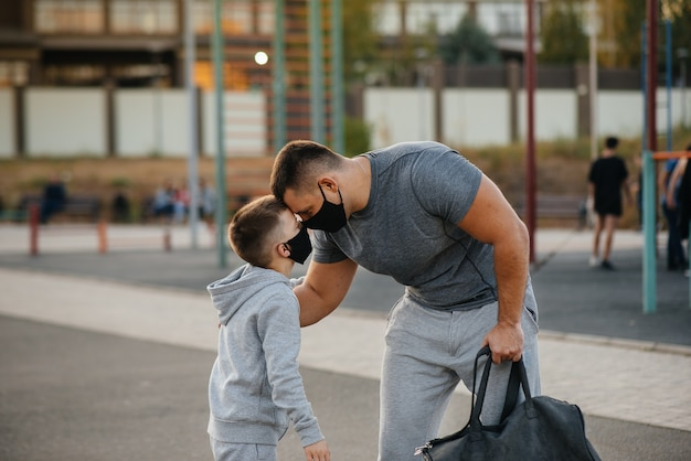 Отец и ребенок стоят на спортивной площадке в масках после тренировки во время заката.