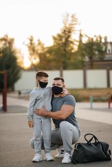 아버지와 자식은 일몰 동안 훈련 후 마스크에 스포츠 필드에 서 있습니다.