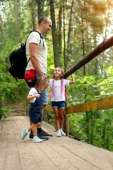 한 아버지와 그의 딸들이 숲 지역의 생태 산책로를 따라 걷고 있다