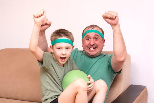 Отец и сын в зеленых банданах и футболках сидят на бежевом диване и эмоционально болеют за футбольную команду по телевизору.