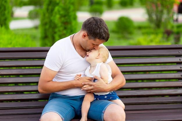 아버지는 야외 벤치에 있는 공원에서 우는 아들을 진정시키고 아버지와 보살핌의 개념