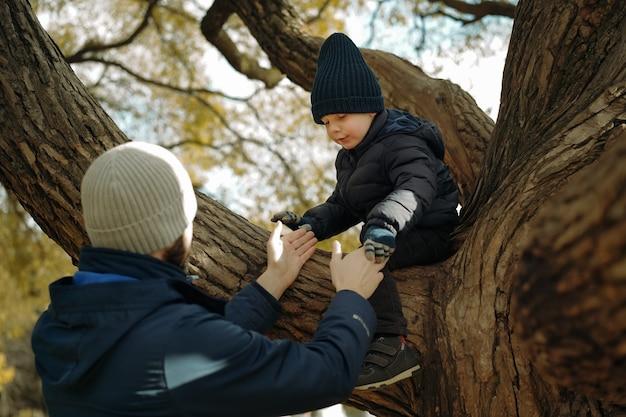 그의 귀여운 작은 아들이 선택적 초점으로 공원 이미지에서 나무 아래로 내려가는 것을 돕는 아버지