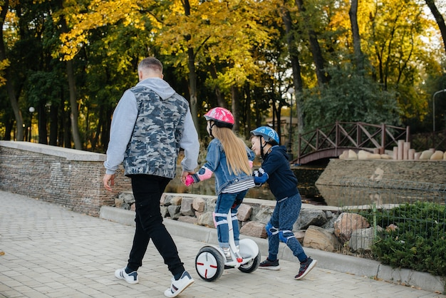 Отец помогает и учит своих маленьких детей кататься на сегвее в парке на закате. семейный отдых в парке.