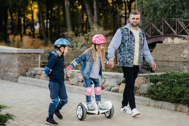 아버지는 일몰 동안 공원에서 세그웨이를 타도록 어린 자녀를 돕고 가르치고 있습니다.