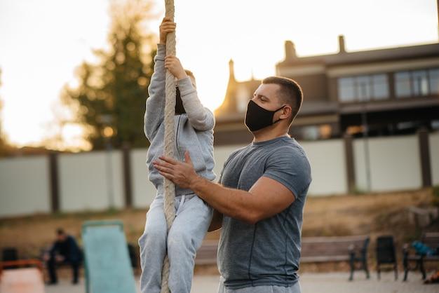 아버지는 일몰 동안 마스크를 쓰고 운동장에서 아들이 밧줄을 오르는 것을 돕습니다. 건강한 육아와 건강한 생활 방식.
