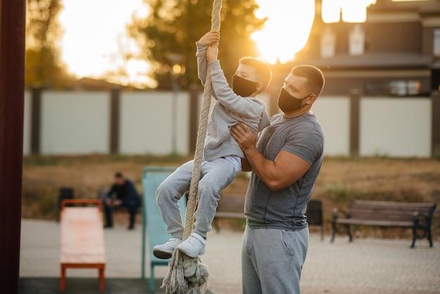 Отец помогает сыну подняться по канату на спортивной площадке в масках на закате.