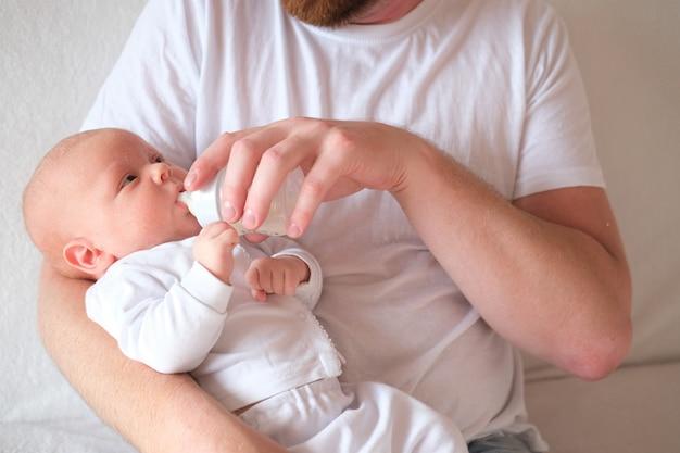父親は生まれたばかりの赤ちゃんを抱き、哺乳瓶で育てます。