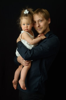 Отец держит на руках свою маленькую годовалую дочь