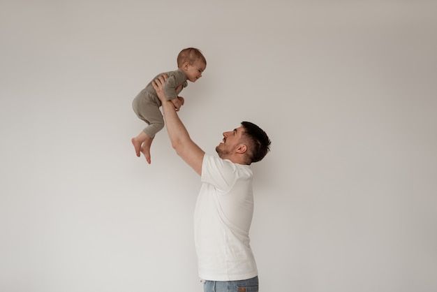 白い壁を背景に産休中の父親が子供と遊んで、上を持ち上げ、腕を伸ばしたまま、笑顔で遊んでいます。