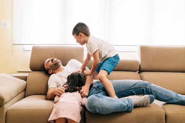父親は自宅の居間のソファで遊んで子供たちと幸せに楽しんでいます