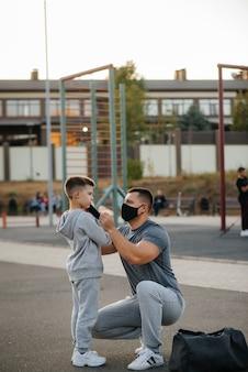 일몰 동안 훈련을 마친 아버지는 놀이터에서 아들에게 마스크를 씌운다