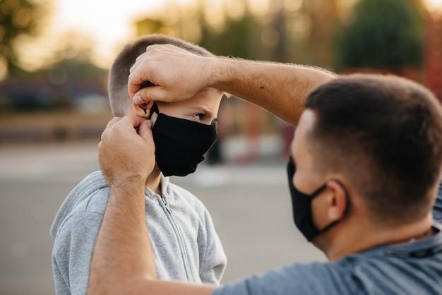 父親は日没時にトレーニングした後、遊び場で息子にマスクをかけます。