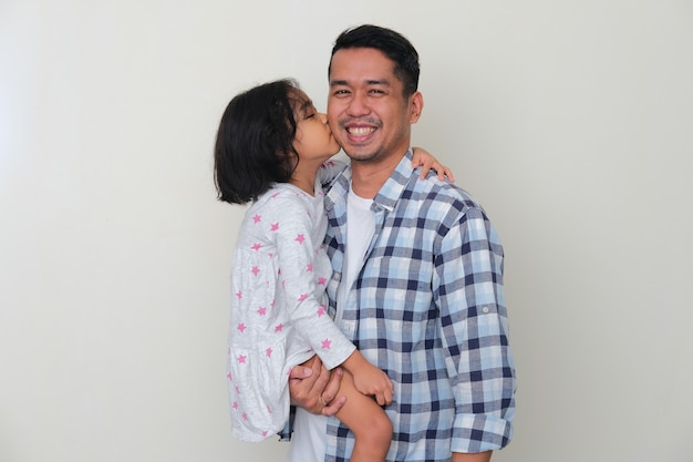 Отец улыбается счастливым, а его дочь целует его в щеку. изолированные на белом