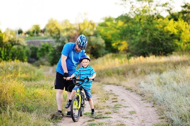 아버지가 보호 헬멧을 쓴 아들의 어린 아이에게 자전거 타기를 가르치고 있습니다.