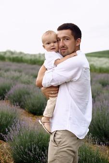 한 아버지가 아들과 함께 라벤더 밭을 걷고 있습니다.